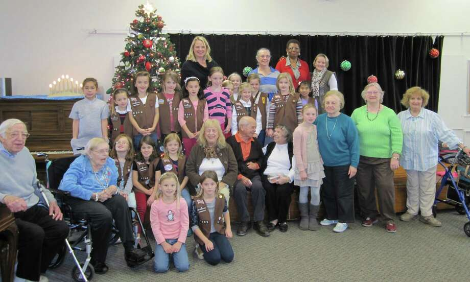 Ox Ridge School's second-grade Brownie Troop No. 50265 visited the Darien Senior Center Dec. 4 to share some holiday cheer. The Brownies and seniors listened to festive music and became acquainted. Photo: Contributed Photo, Contributed / Darien News