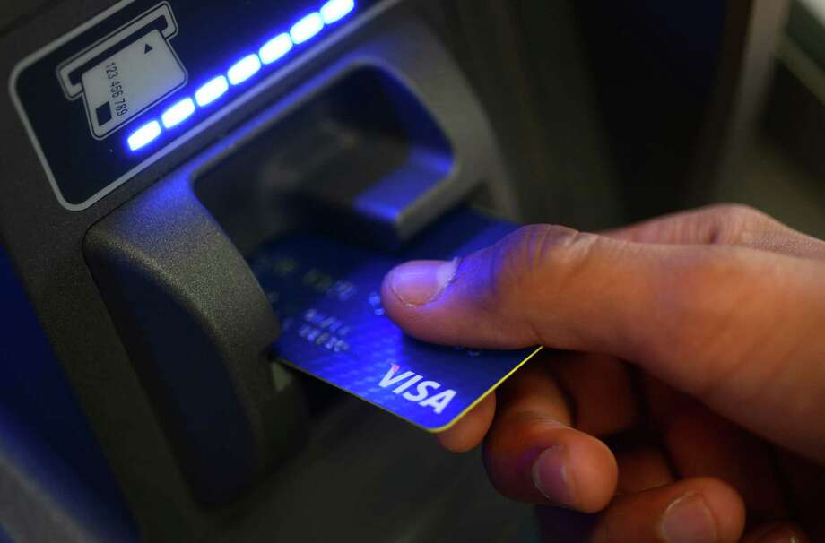 A  photo illustration shows a customer scanning a credit card into a gas station ATM in Derby, Conn. on Friday, Dec. 20, 2013. Photo: Autumn Driscoll, Autumn Driscoll/Photo Illustrati / Connecticut Post
