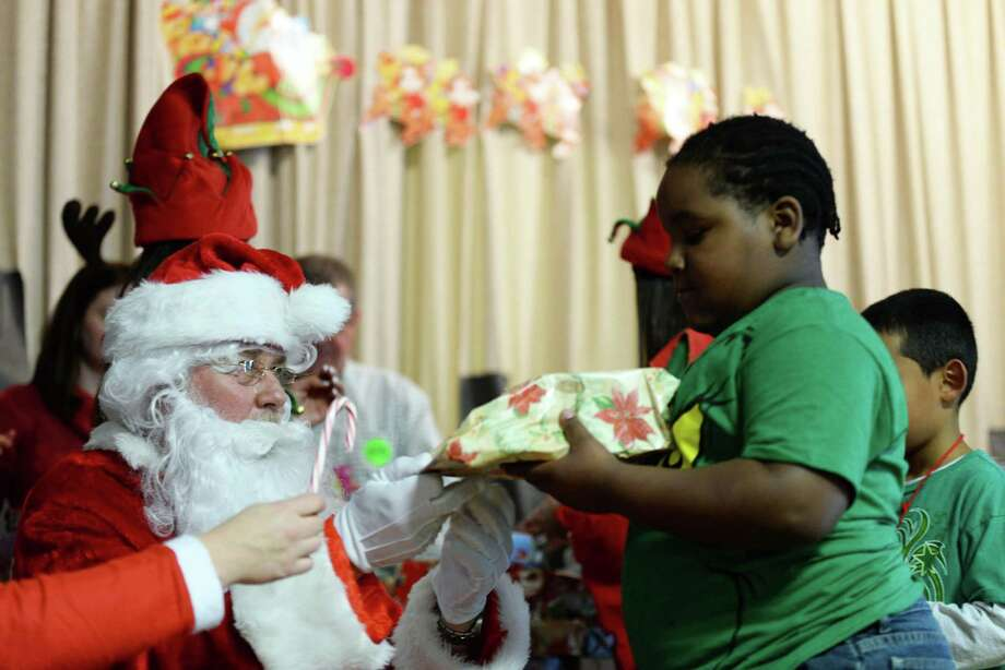 Students of Hall elementary school receiving gifts from Santa.  The gifts were donated by Sikorsky Finance Women's Forum. Photo: Andrew Merrill