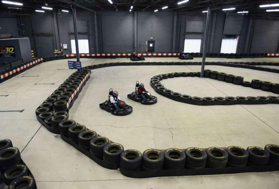 Karters race around a turn at On Track Karting in Brookfield, Conn. on Friday, Dec. 20, 2013.  The indoor go kart racing facility features an 1,800-foot track that is one of the longest and fastest indoor tracks on the East Coast.  On Track Karting has an adult racing league every Thursday night and a junior winter league on Sunday starting January 5, as well as a monthly 60-minute Ironman race.  The facility also hosts parties and large group events. Photo: Tyler Sizemore / The News-Times