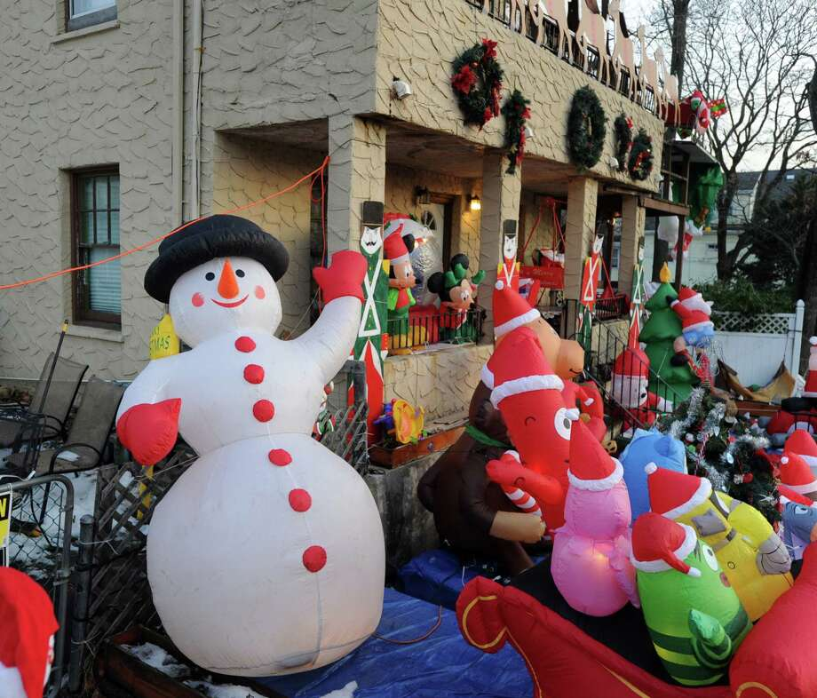 "A waving inflatable snowman is part of the Christmas-themed decorated home of the Church family on Harold Avenue in the Chickahominy section of Greenwich that is the masterwork of Bill Church said his daughter, Tara Church, who was at home Friday, Dec. 20, 2013. Tara Church said ""there are over 50 items and various other displays. A lot of it runs off a wireless remote control."" Church says her family keeps the display up until a few days after the new year. Photo: Bob Luckey / Greenwich Time"