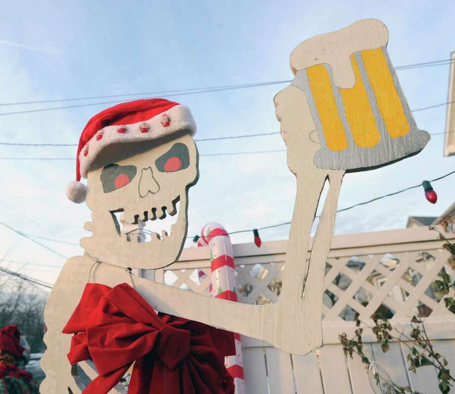 "A cut-out of a skeleton with a beer mug is part of the unusal Christmas-themed decorated home of the Church family on Harold Avenue in the Chickahominy section of Greenwich that is the masterwork of Bill Church said his daughter, Tara Church, who was at home Friday, Dec. 20, 2013. Tara Church said ""there are over 50 items and various other displays. A lot of it runs off a wireless remote control."" Church says her family keeps the display up until a few days after the new year. Photo: Bob Luckey / Greenwich Time"