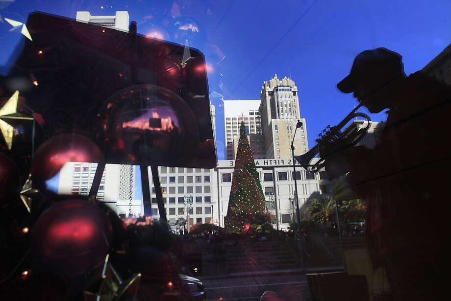 Jim Eyres plays his coronet next to his donation kettle in front of Macy's on Geary Street in San Francisco. Photo: Mike Kepka, The Chronicle
