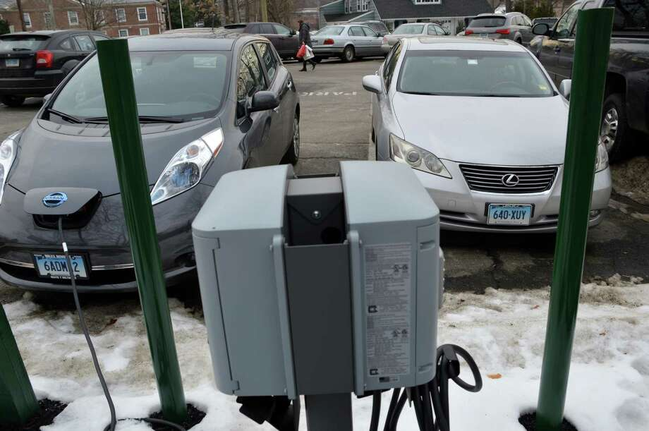 One of the two electric vehicle charging stations at the Bay Street parking lot, in this photo, is being used to recharge an EV while the other charging is blocked by a gas-powered car. Photo: Jarret Liotta / Westport News contributed