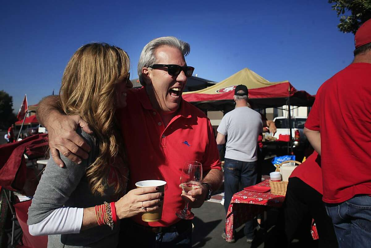 Tailgate friends, Mendy Calegari and Don Figone, laugh before the game on Dec. 1, 2013, in San Francisco, Calif.