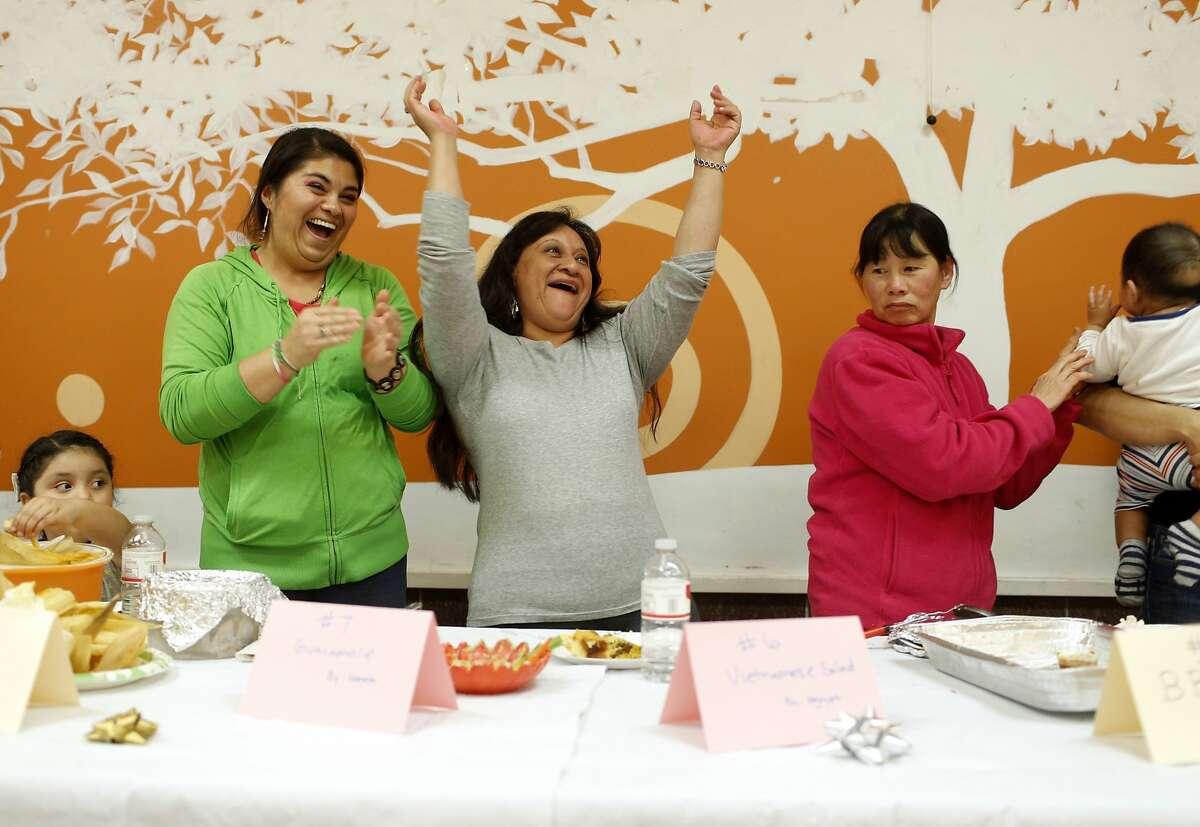 Contestants Magdalena Macias (left) and Norma (center) celebrate after Norma's guacamole won third place in the year-end cooking contest at the 201 Turk St. apartment building, Thursday, December 19, 2013 in San Francisco, Calif. Norma has been cooking entires all five years the contest has been held and this was her first time winning.