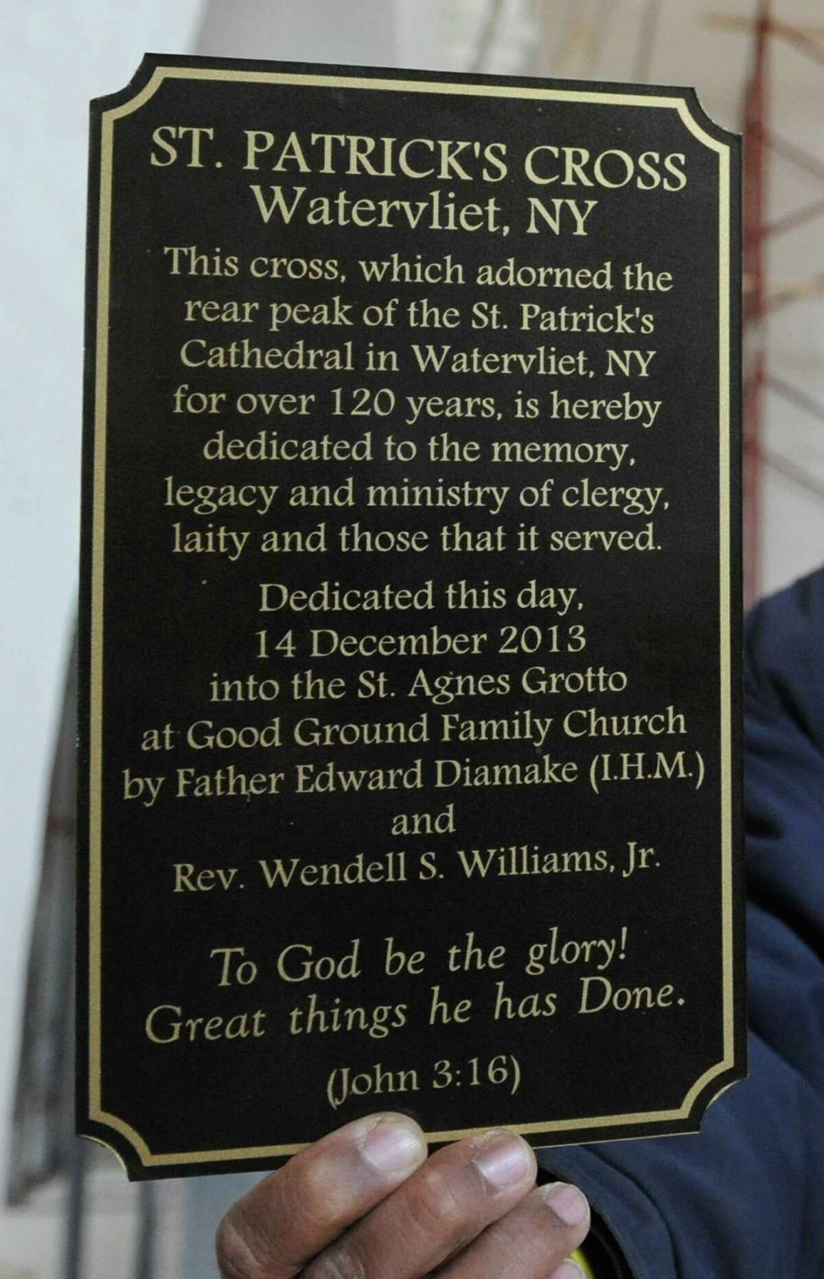 Pastor Wendell Williamson holds a dedication plaque that will be glued to the base of the cross in the former St. Agnes grotto outside the Good Ground Family Church on Wednesday, Dec. 18, 2013, in Cohoes N.Y. The cross came from the rear peak of the St. Patrick's cathedral in Watervliet. (Lori Van Buren / Times Union)