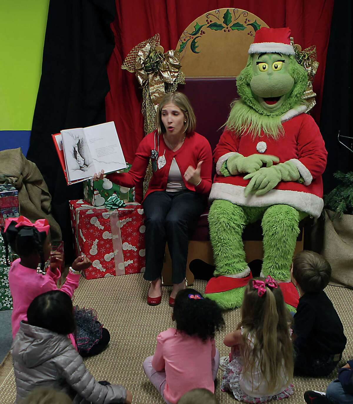 """Houston Children's Museum librarian Kallie Benes reads """"How The Grinch Stole Christmas"""" during Story Time with the Grinch at the Children's Museum of Houston."""