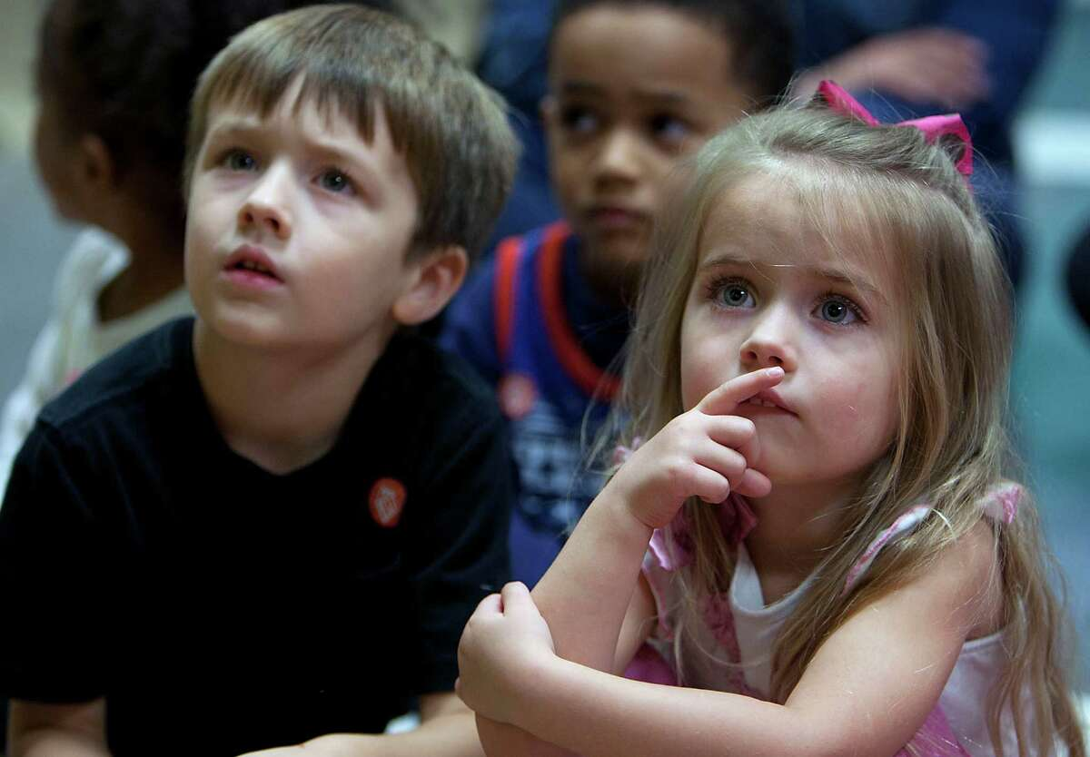 Jacob Elrod left, and his sister Tori Elrod right, look on the reading of How The Grinch Stole Christmas during Story Time with the Grinch at the Children's Museum of Houston Wednesday, Dec. 18, 2013, in Houston. ( James Nielsen / Houston Chronicle )