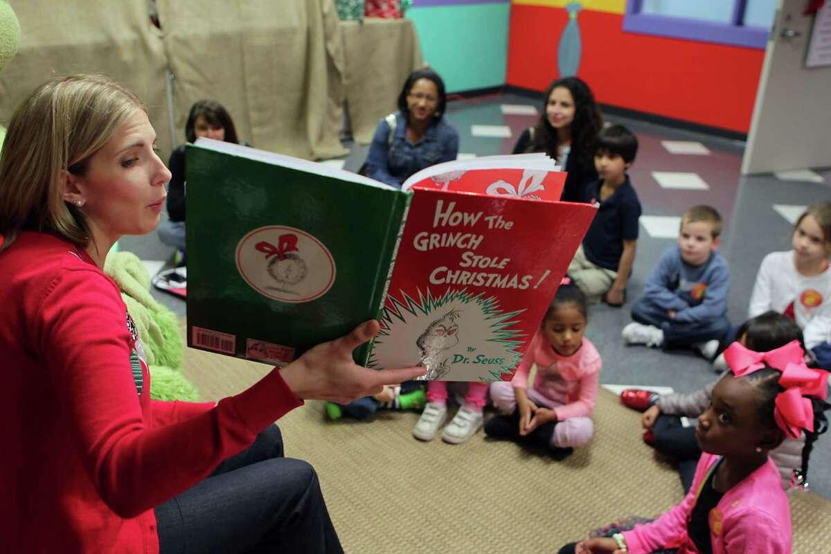 Houston Children's Museum librarian Kallie Benes left, reads How The Grinch Stole Christmas during Story Time with the Grinch at the Children's Museum of Houston Wednesday, Dec. 18, 2013, in Houston. ( James Nielsen / Houston Chronicle )