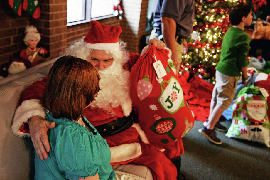 Santa hands out Christmas gifts to the children of Girls' Haven Friday. In its 10th year the Jefferson County Deputy Sheriff's Association and partners, distributed $10,000 worth of toys to 20 foster girls. Michael Rivera.@michaelrivera88