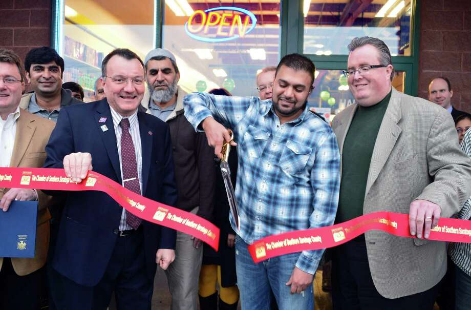 Owner Tahir Sial, center, with Pete Bardunias, left, of the Chamber of Southern Saratoga County and Halfmoon Supervisor Kevin Tollison, cuts the ribbon Friday, Dec. 20, 2013, to open of the Halal Meat Market on Route 9 in Halfmoon, N.Y.  Halal Meat Market is the first such store in the Clifton Park area. It will sell ethnic spices, produce, and other items including halal (Muslim Kosher) meat.  (John Carl D'Annibale / Times Union) Photo: John Carl D'Annibale / 00025084A