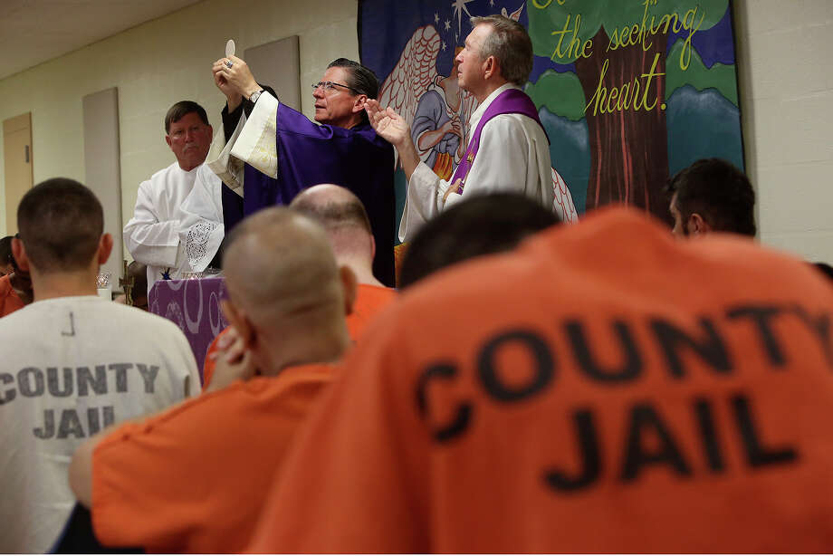 Archbishop Gustavo Garcia-Siller, center, leads mass for inmates at the Bexar County Adult Detention Facility in San Antonio on Friday, Dec. 20, 2013. With him are Deacon Bob Leibrecht, left, and Chaplain Carl Schindler, right. Photo: Lisa Krantz, San Antonio Express-News / San Antonio Express-News