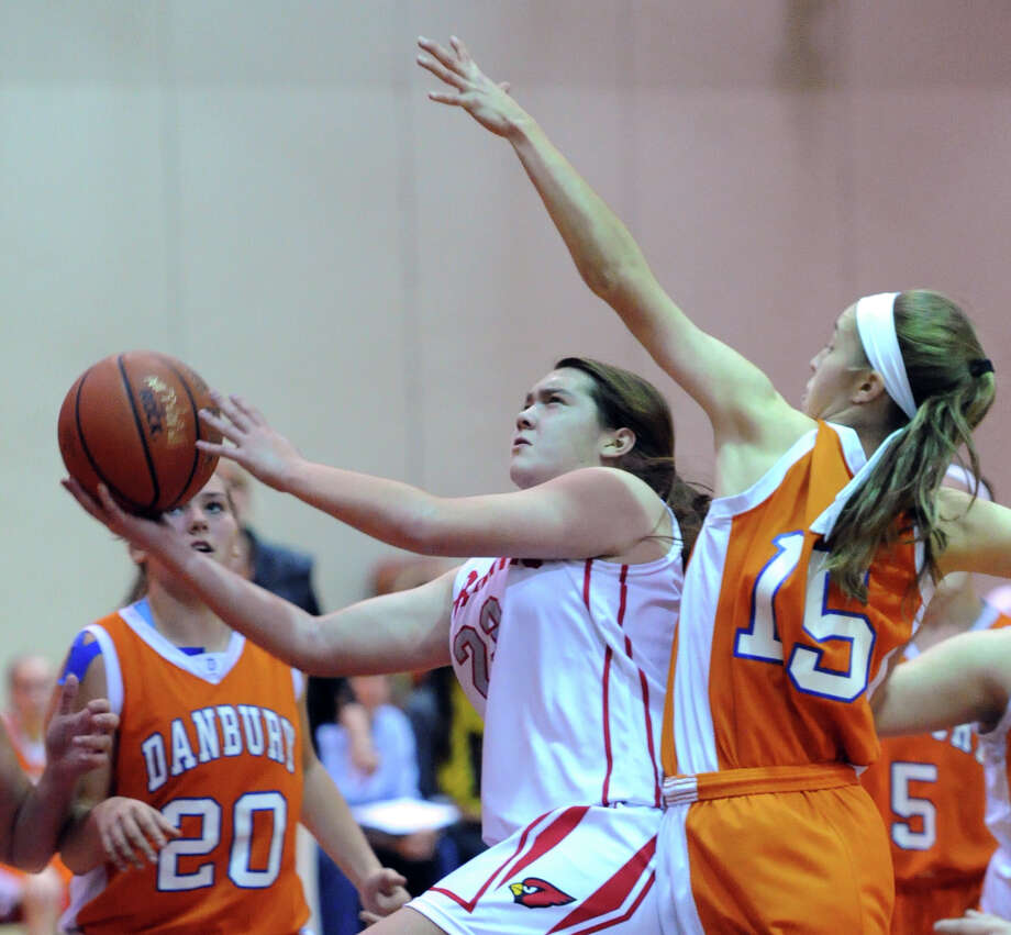 At center, Jamie Kockenmeister (# 23) of Greenwich goes in for a lay-ip while being defended by Danbury's Rebecca Gartner (# 15), right, during the girls high school basketball game between Greenwich High School and Danbury High School at Greenwich, Friday night, Dec. 20, 2013. At left is Allie Smith (# 20) of Danbury. Photo: Bob Luckey / Greenwich Time