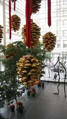 """Financial District towers with large holiday decorations include 101 California St. with its tree ornaments, 345 California St. with a huge wreath and 101 2nd St. with huge pine cones hanging in its public """"art pavilion."""""""