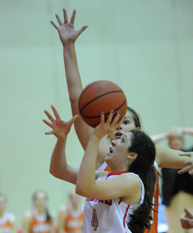 Foreground, Leigh Galletta of Greenwich (# 4) goes in for a lay-up during the girls high school basketball game between Greenwich High School and Danbury High School at Greenwich, Friday night, Dec. 20, 2013. Photo: Bob Luckey / Greenwich Time