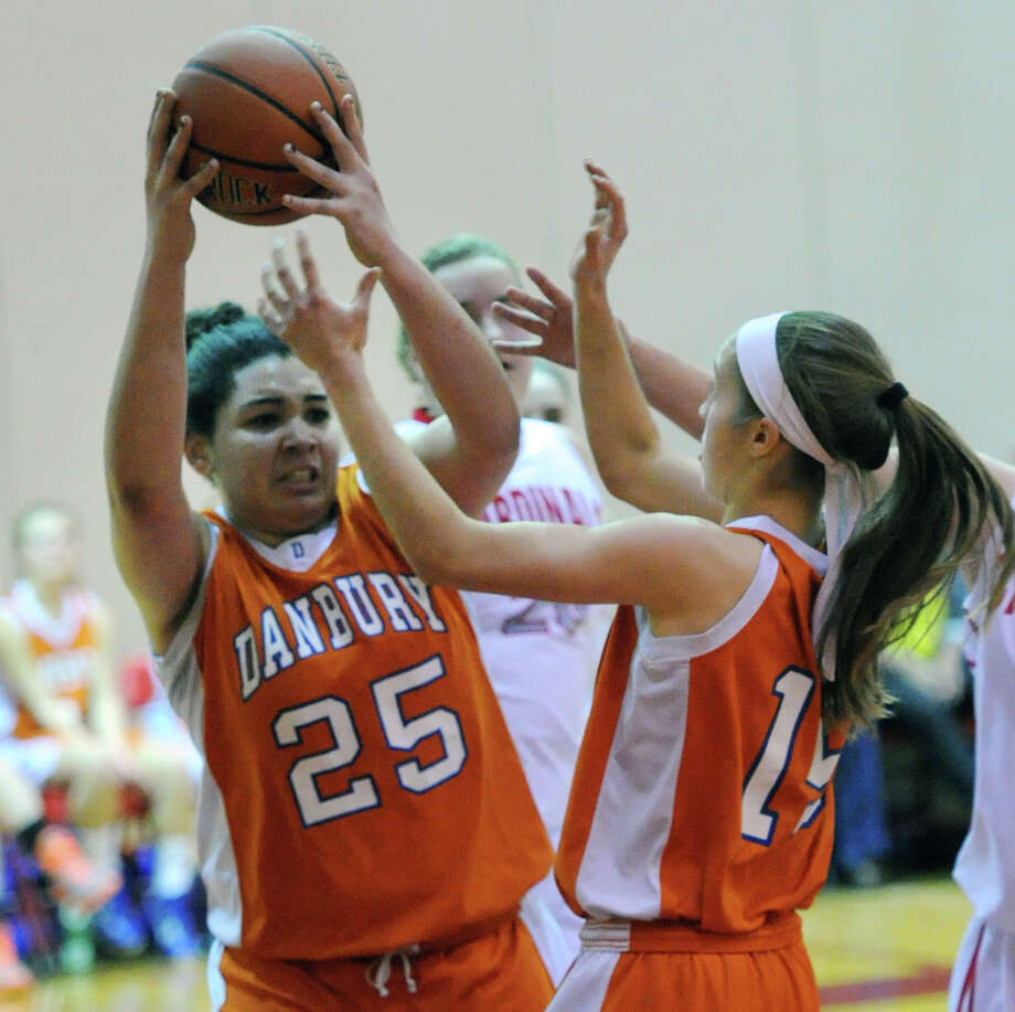 At left, Kayla Handberry (# 25) of Danbury rebounds the ball during the girls high school basketball game between Greenwich High School and Danbury High School at Greenwich, Friday night, Dec. 20, 2013. Photo: Bob Luckey / Greenwich Time