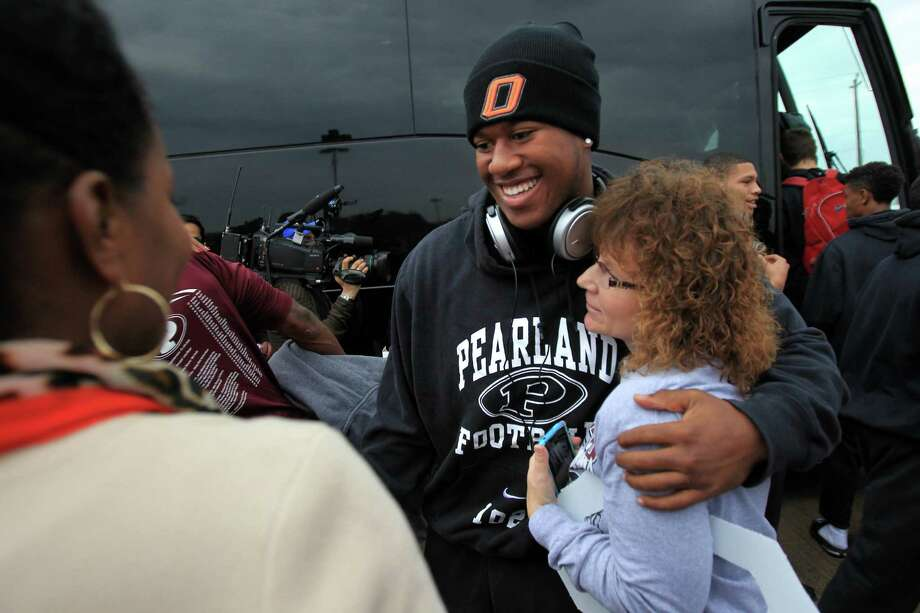 Pearland Oiler Football player (#19) Justin Phillips is embraced by Roxanne Cook as family, students, and faculty send off the Pearland Oilers Varsity Football Team to the State game in Dallas on Friday, Dec. 20, 2013, in Pearland. Photo: Mayra Beltran, Houston Chronicle / © 2013 Houston Chronicle