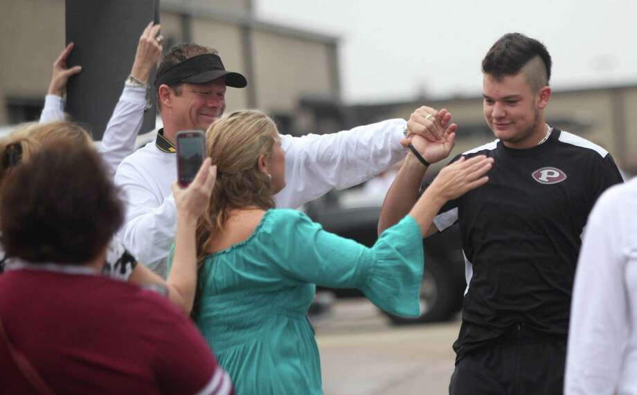 Pam Boegler reaches out to her son Zach Boegler as family, students, and faculty send off the Pearland Oilers Varsity Football Team on their day to play State in Dallas on Friday, Dec. 20, 2013, in Pearland. Photo: Mayra Beltran, Houston Chronicle / © 2013 Houston Chronicle