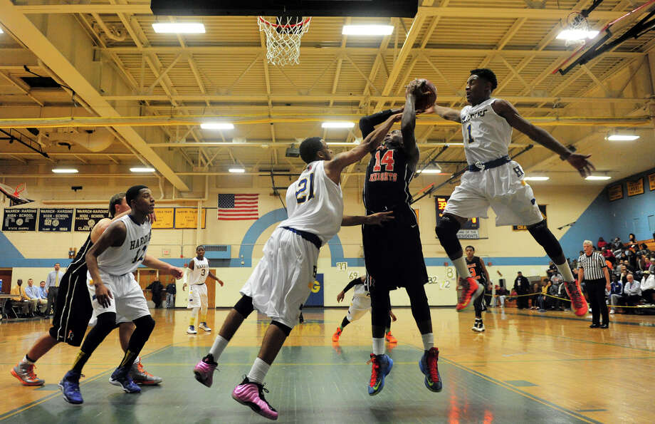 Harding's Kanard Codrington, center, and teammate T.J. Killings, right, block a shot attempt by Stamford's Kenny Wright, during boys basketball action in Bridgeport, Conn. on Friday December 20, 2013. Photo: Christian Abraham / Connecticut Post