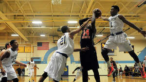 Harding's Kanard Codrington, center, and teammate T.J. Killings, right, block a shot attempt by Stamford's Kenny Wright, during boys basketball action in Bridgeport, Conn. on Friday December 20, 2013.