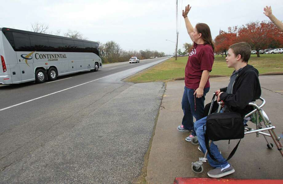 """""""I just wanted to come cheer them on"""" says student Jakob Sifford, 15, with Lynn Anderson, teacher aid, as they send off the Pearland Oilers Varsity Football Team on their way to play State in Dallas on Friday, Dec. 20, 2013, in Pearland. Photo: Mayra Beltran, Houston Chronicle / © 2013 Houston Chronicle"""