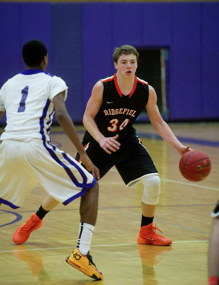 Ridgefield's Charles Irwin controls the ball during Friday's basketball game against Westhill in Stamford, Conn., on December 20, 2013. Photo: Lindsay Perry / Stamford Advocate
