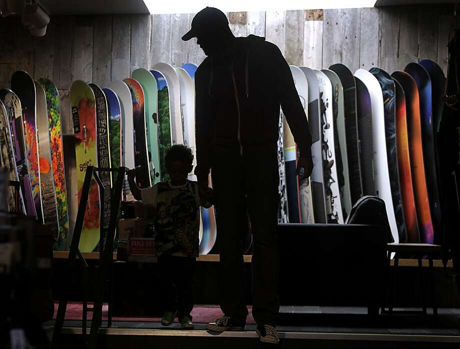 Derrick Phipps and his son Logan walk past snowboards displayed at a new Burton snowboarding shop in Berkeley, Calif. on Saturday, Nov. 16, 2013. The 2,300 sq. ft. location on Berkeley's trendy Fourth Street is the first of two flagship stores to open in the Bay Area. Photo: Paul Chinn, The Chronicle