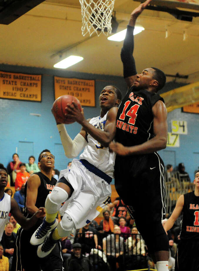 Harding's Terrence Rogers looks to score two as Stamford's Kenny Wright blocks, during boys basketball action in Bridgeport, Conn. on Friday December 20, 2013. Photo: Christian Abraham / Connecticut Post
