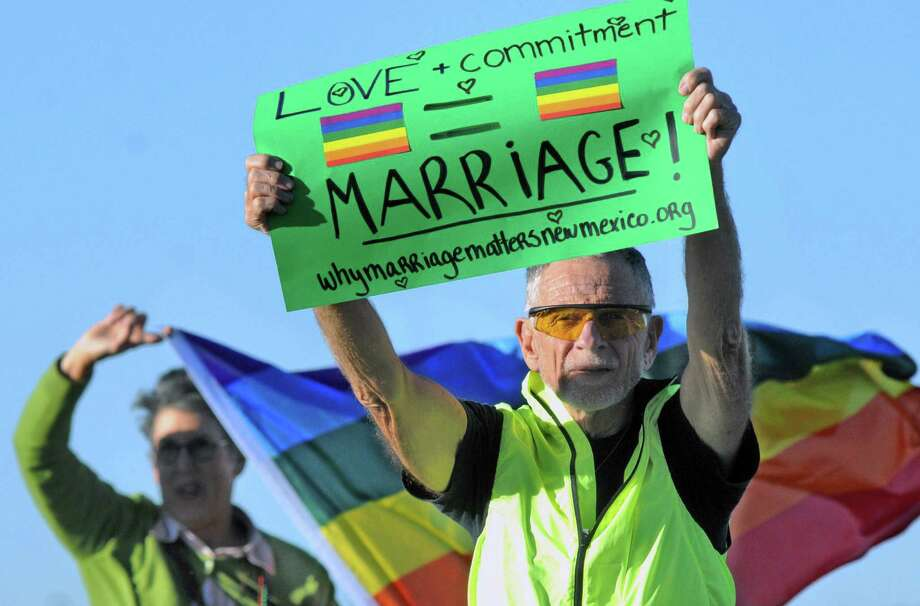 Carl Smith of Las Cruces, N.M., holds up a sign in support of same-sex marriage as Jean Ber- lowitz waves a flag during a rally to celebrate the New Mexico Supreme Court ruling Thursday. Photo: Robin Zielinski / Las Cruces Sun-News / Las Cruces Sun-News