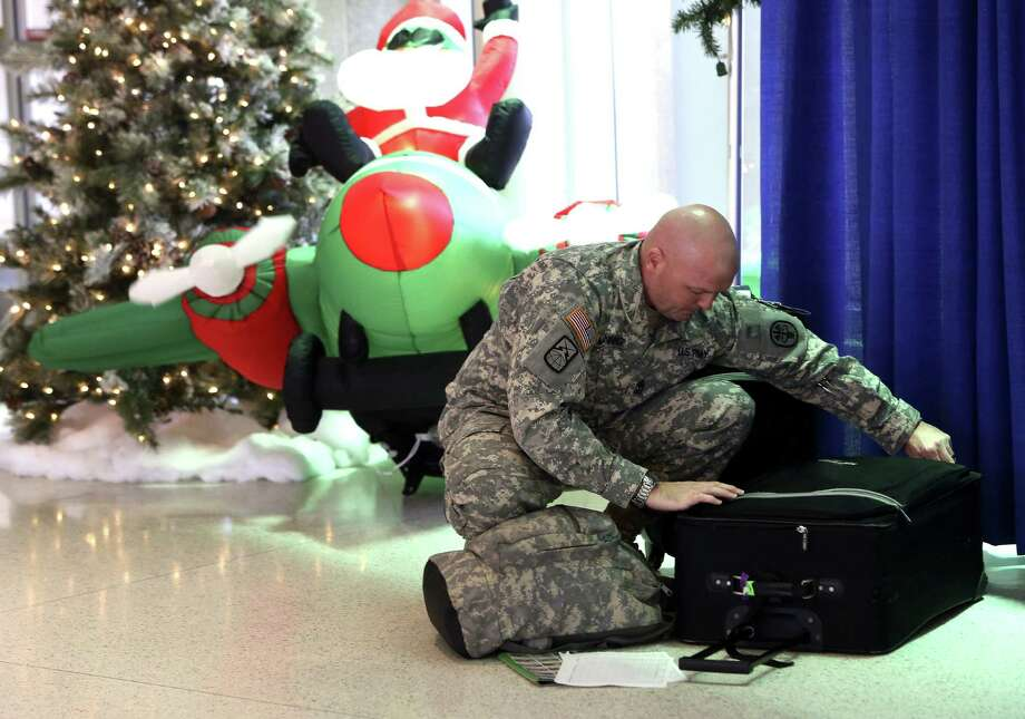 First Sgt. John Manning arranges his bags before checking in for his flight home to Hawaii. Thousands of soldiers, sailors and airmen were expected to leave S.A. for the holidays. Photo: Helen L. Montoya / San Antonio Express-News / SAN ANTONIO EXPRESS-NEWS