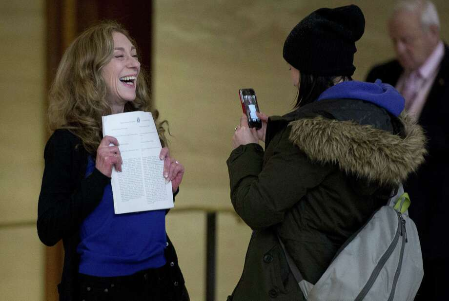 Former prostitute Valerie Scott, one of the three principles in the case, holds a copy of the ruling striking down Canada's prostitution laws at the country's Supreme Court in Ottawa. Photo: Associated Press / The Canadian Press