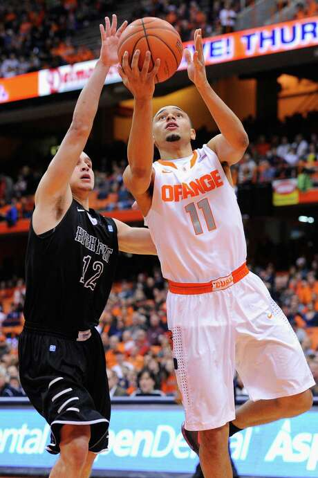 Syracuse's Tyler Ennis gets past High Point's Jorge Perez-Laham to take a first-half shot. Photo: Rich Barnes / Getty Images / 2013 Getty Images