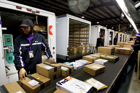 Wesley Springfellow sorts packages at FedEx's Holly Hall Drive warehouse. Delivery services are busier as online shopping grows.