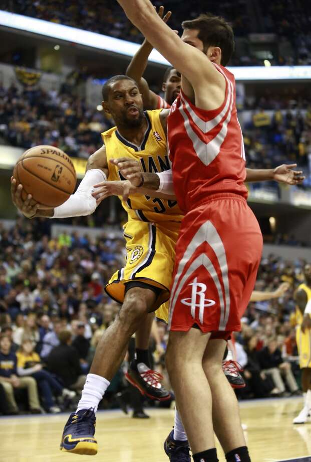 Pacers guard C.J. Watson, left, passes the basketball around Rockets forward Omri Casspi. Photo: R Brent Smith, Associated Press