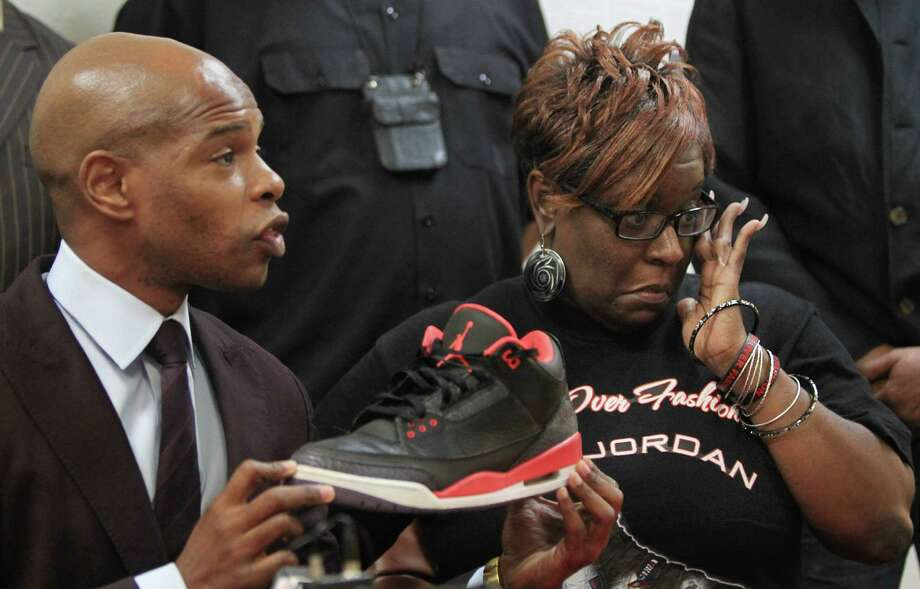 Deric Muhammad addresses the media with Dazie Williams, urging parents to accompany children when they go to purchase Air Jordans. Photo: Mayra Beltran, Staff / © 2013 Houston Chronicle