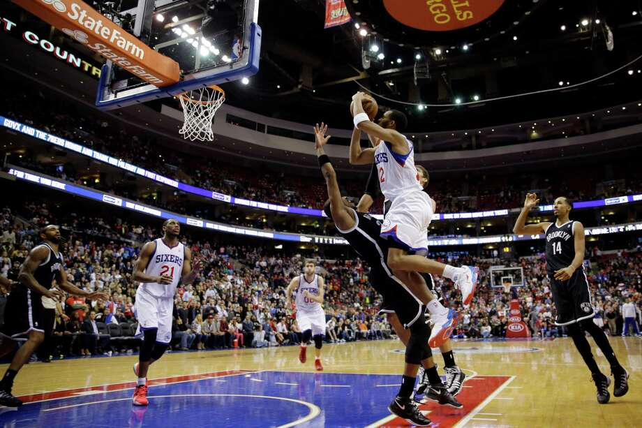 Philadelphia 76ers' Evan Turner, center right, shoots the game-winning basket over Brooklyn Nets' Paul Pierce in the final seconds of overtime in an NBA basketball game, Friday, Dec. 20, 2013, in Philadelphia. The 76ers' won 121-120 in overtime. (AP Photo/Matt Slocum) ORG XMIT: PXC111 Photo: Matt Slocum / AP