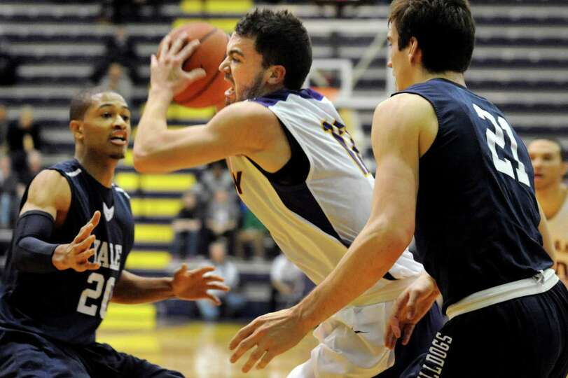 UAlbany's Peter Hooley, center, looks to pass as Yale's Javier Duren, left, and Nick Victor defend d