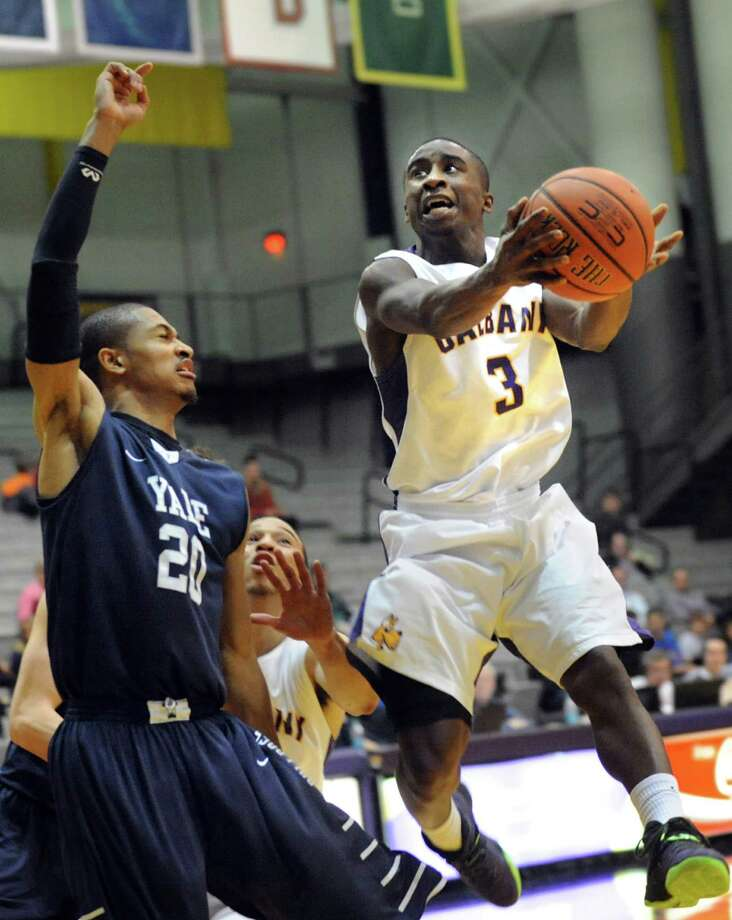 UAlbany's D.J. Evans, right, goes to the hoop as Yale's Javier Duren defends during their basketball game on Friday, Dec. 20, 2013, at SEFCU Arena in Albany, N.Y (Cindy Schultz / Times Union) Photo: Cindy Schultz / 00024943A