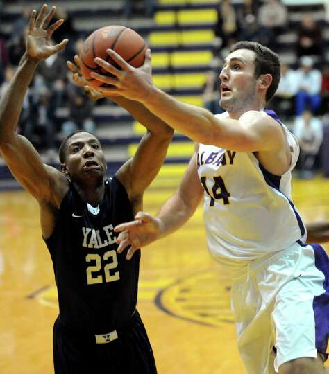UAlbany's Sam Rowley, right, goes to the hoop as Yale's Justin Sears defends during their basketball