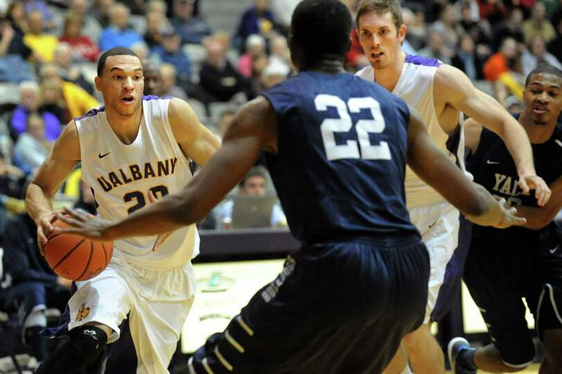 UAlbany'sGary Johnson, left, controls the ball as Yale's Justin Sears, center, defends during their