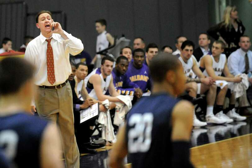 UAlbany's coach Will Brown, left, instructs his team during their basketball game against Yale on Fr
