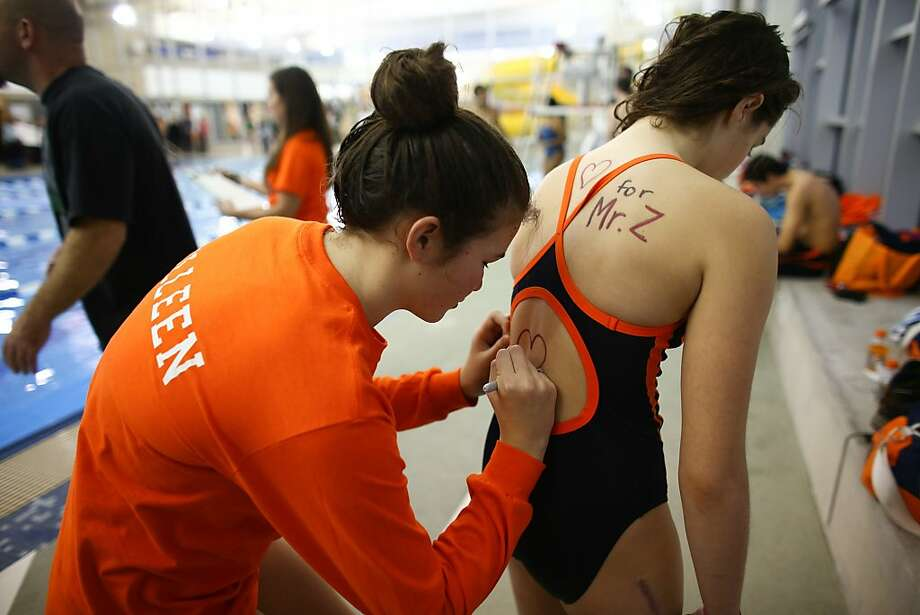 Swim team members write messages of support for their coach on each other's backs during a swim meet at the Rainier Beach Community Center, Friday, Dec. 20, 2013, in Seattle. Eastside Catholic's Vice Principal Mike Zmuda, who coached the team, resigned from the school after officials with the Seattle archdiocese discovered that he was in a same-sex marriage. He was told the marriage violated his contract. (AP Photo/seattlepi.com, Joshua Trujillo) Photo: Joshua Trujillo, Associated Press