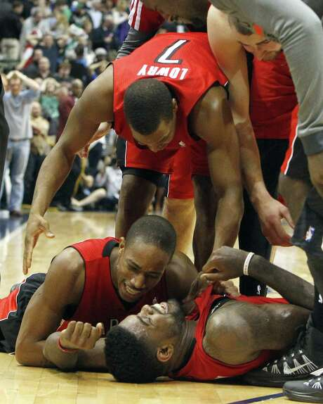 Toronto's DeMar DeRozan, bottom left, Kyle Lowry (7) and Amir Johnson were all smiles after holding on to defeat Dallas a 109-108 in overtime. Photo: Richard Rodriguez, MBR / Fort Worth Star-Telegram