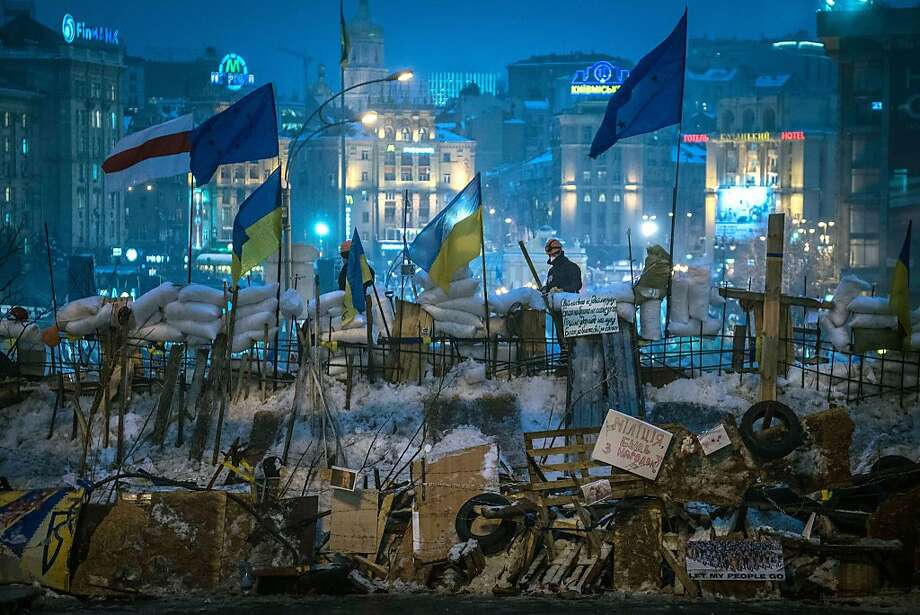 Ukrainian and European Union flags fly over the newly-erected barricades at Independence Square in Kiev, Ukraine, Dec. 12, 2013. Demonstrators streaming in from Ukraine's West reinvigorated protests Thursday, as the showdown over closer ties to the EU worsens the divide between Ukraine's West and the East, where ethnic Russians provide strong support for President Viktor Yanukovych. Photo: Sergey Ponomarev, New York Times