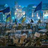 Ukrainian and European Union flags fly over the newly-erected barricades at Independence Square in Kiev, Ukraine, Dec. 12, 2013. Demonstrators streaming in from Ukraine's West reinvigorated protests Thursday, as the showdown over closer ties to the EU worsens the divide between Ukraine's West and the East, where ethnic Russians provide strong support for President Viktor Yanukovych.
