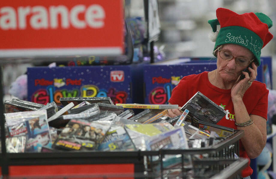 Julie Cheatwood talks on the phone while doing some last-minute shopping in San Antonio before she and her family got set to travel to Virginia for Christmas. Photo: Photos By John Davenport / San Antonio Express-News / ©San Antonio Express-News/Photo may be sold to the public