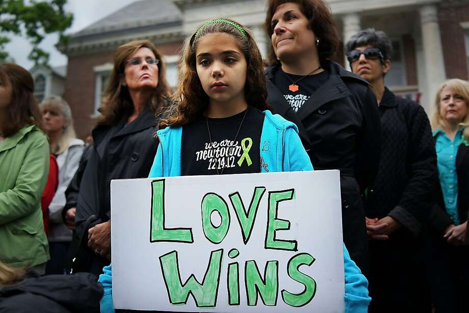 Cecilia Floros, 10, of Newtown attends a remembrance event on the six month anniversary of the massacre at Sandy Hook Elementary School on June 14, 2013 in Newtown, Connecticut. A a 26-second moment of silence was observed to honor the 20 children and six adults who were killed at the school on Dec. 14. The event also included the reading of the names of over 6,000 people who have been killed by gun violence since the massacre in Newtown. The reading of names is expected to take 12 hours. Photo: Spencer Platt, Getty Images