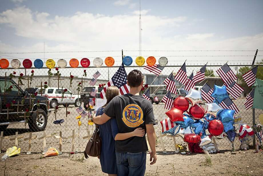 Freddy Warneke, right, brother of William Warneke, one of the 19 firefighters killed battling a fire on Sunday, at a makeshift memorial outside Fire Station 7, home of the Granite Mountain Hotshots, in Prescott, Ariz., July 2, 2013. Nineteen of the 20 members of the Granite Mountain Hotshots perished fighting a fierce wilderness fire outside the old gold mining village of Yarnell, Ariz. Photo: Max Whittaker, New York Times