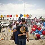 Freddy Warneke, right, brother of William Warneke, one of the 19 firefighters killed battling a fire on Sunday, at a makeshift memorial outside Fire Station 7, home of the Granite Mountain Hotshots, in Prescott, Ariz., July 2, 2013. Nineteen of the 20 members of the Granite Mountain Hotshots perished fighting a fierce wilderness fire outside the old gold mining village of Yarnell, Ariz.